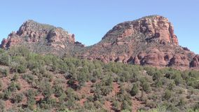 Arizona, Sedona, A pan across a red rock formation in Sedona with trees and houses