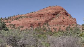 Arizona, Sedona, A pan across Sugarloaf Mountain with trees and bushes in the foreground