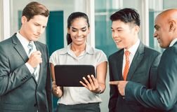 Pan Asian and Caucasian business team looking at tablet computer Royalty Free Stock Photography