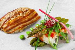 Pan-asian cuisine with sea eel, asparagusand and p Stock Photography