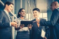 Pan Asian e o negócio caucasiano team olhando o tablet pc fotografia de stock