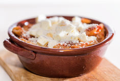 Pan baked pasta. Penne with tomato sauce with sausage, mozzarella and Parmesan botched baked in earthenware pot royalty free stock photos