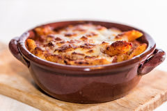 Pan baked pasta. Penne with tomato sauce with sausage, mozzarella and Parmesan botched baked in earthenware pot royalty free stock image