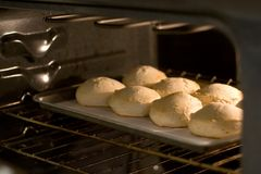 Pan of biscuits in oven. Pan of biscuits in lighted oven Royalty Free Stock Images