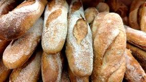 Pan, bollos y otros productos de la panader?a del color de oro en estantes de una tienda en el movimiento metrajes