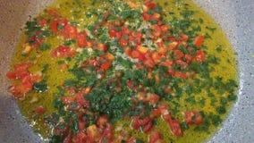 Pan briet mit Öl, Tomate, Petersilie, Knoblauch stock footage