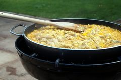 Pan of chicken paella cooking on an outdoor gas cooker.  Stock Images