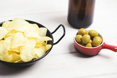 Pan with chips, small dish with olives and beer bottle standing on pale gray wooden table. Stock Photos