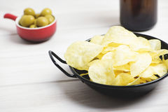 Pan with chips, small dish with olives and beer bottle standing on pale gray wooden table. Stock Image