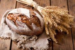 Pan cocido fresco con los oídos del trigo Fotos de archivo libres de regalías
