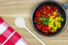 Pan with colorful sliced paprikas on wooden background Royalty Free Stock Photo