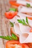 Pan con el jamón cortado, los tomates frescos y el perejil Imagen de archivo libre de regalías