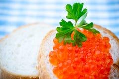 Pan con el queso cremoso fresco y el caviar rojo en la tabla Imagenes de archivo