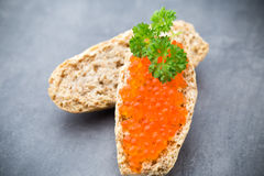 Pan con el queso cremoso fresco y el caviar rojo en la tabla Imagen de archivo libre de regalías