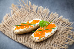 Pan con el queso cremoso fresco y el caviar rojo en la tabla Fotos de archivo libres de regalías