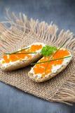 Pan con el queso cremoso fresco y el caviar rojo en la tabla Foto de archivo