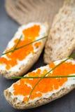 Pan con el queso cremoso fresco y el caviar rojo en la tabla Fotos de archivo