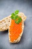 Pan con el queso cremoso fresco y el caviar rojo en la tabla Fotografía de archivo