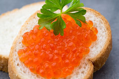 Pan con el queso cremoso fresco y el caviar rojo en la tabla Foto de archivo libre de regalías
