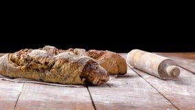 Pan con el rodillo en la tabla de madera con el fondo negro Foto de archivo