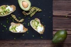 Pan con las rebanadas de aguacate y de queso cremoso imagenes de archivo