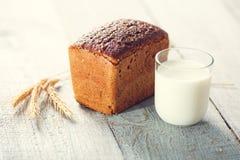 Pan con leche y espiguillas del trigo en tableros de madera Imagen de archivo libre de regalías