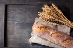 Pan con los oídos del trigo en la tabla de madera Fotografía de archivo libre de regalías