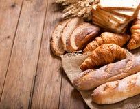 Pan con los oídos del trigo en la tabla de madera Imagen de archivo