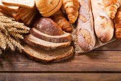 Pan con los oídos del trigo en la tabla de madera, visión superior Imagenes de archivo