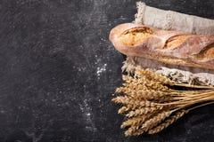 Pan con los oídos del trigo en tablero oscuro Foto de archivo libre de regalías