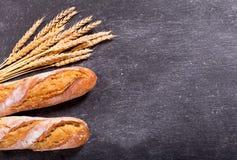Pan con los oídos del trigo en tablero oscuro Fotos de archivo libres de regalías