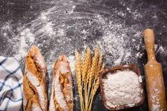 Pan con los oídos del trigo en tablero oscuro Fotografía de archivo