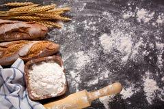 Pan con los oídos del trigo en tablero oscuro Imagen de archivo