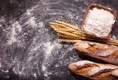 Pan con los oídos del trigo en tablero oscuro Imagen de archivo libre de regalías