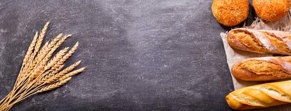Pan con los oídos del trigo en verraco oscuro Foto de archivo libre de regalías