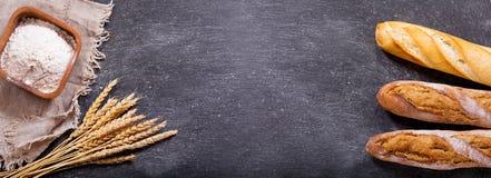 Pan con los oídos del trigo y el cuenco de harina Imágenes de archivo libres de regalías