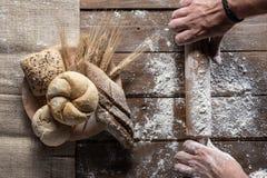 Pan con los o?dos y la harina del trigo en el tablero de madera, visi?n superior fotografía de archivo