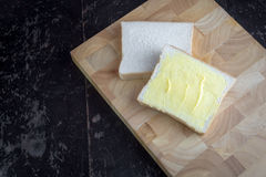 Pan con mantequilla en tabla de cortar Fotografía de archivo