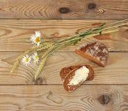 Pan con mantequilla y la manzanilla con los oídos del trigo Foto de archivo libre de regalías