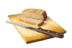 Pan con un cuchillo en una tarjeta de corte de madera Imagen de archivo libre de regalías