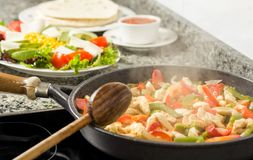Pan cooking vegetables and chicken in the kitchen Stock Photography