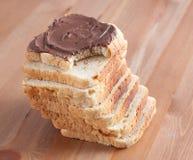 Pan cortado con el chocolate en una tarjeta de madera Fotografía de archivo