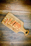 Pan cortado con las semillas de sésamo en un tablero de madera Imagenes de archivo