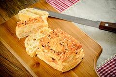Pan cortado con las semillas de sésamo en un tablero de madera fotos de archivo libres de regalías