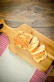 Pan cortado con las semillas de sésamo en un tablero de madera Fotos de archivo