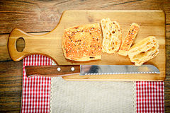 Pan cortado con las semillas de sésamo en un tablero de madera Imagen de archivo