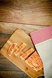Pan cortado con las semillas de sésamo en un tablero de madera fotografía de archivo