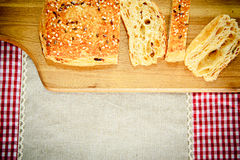 Pan cortado con las semillas de sésamo en un tablero de madera Fotografía de archivo libre de regalías