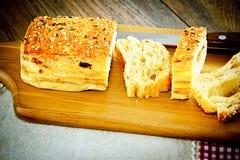 Pan cortado con las semillas de sésamo en un tablero de madera imágenes de archivo libres de regalías