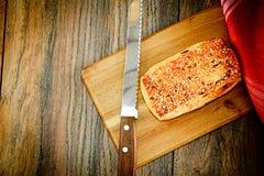 Pan cortado con las semillas de sésamo en un tablero de madera foto de archivo
